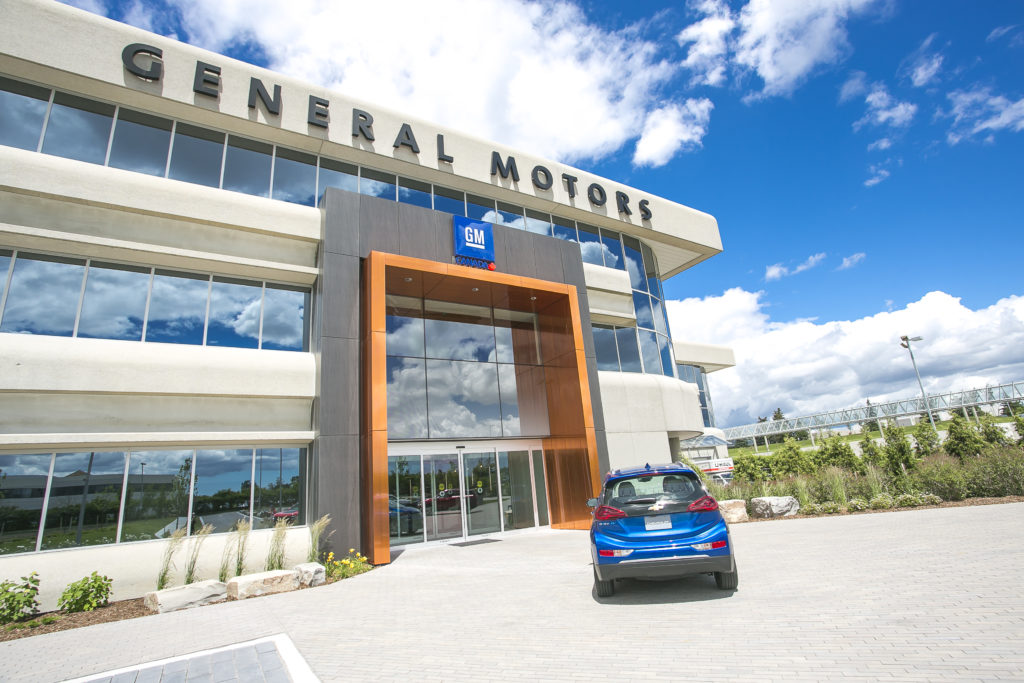 Exterior shot of 101 Mcnabb with General Motors logo showing, sunny blue skies above.